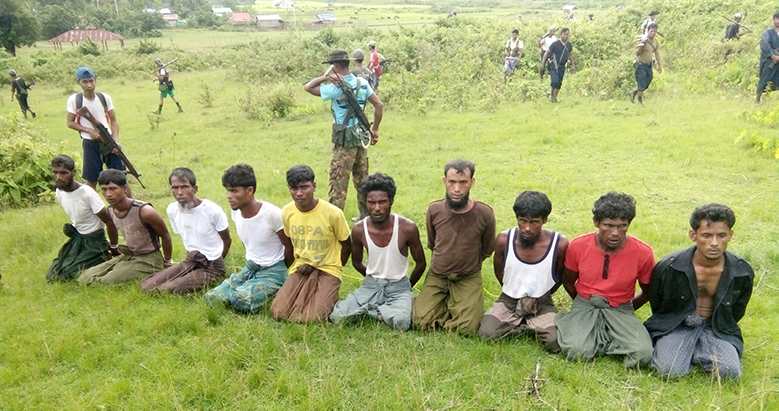 Ten Rohingya Muslim men with their hands bound kneel as members of the Myanmar security forces stand guard in Inn Din village September 2, 2017. Picture taken September 2, 2017. Handout via REUTERS